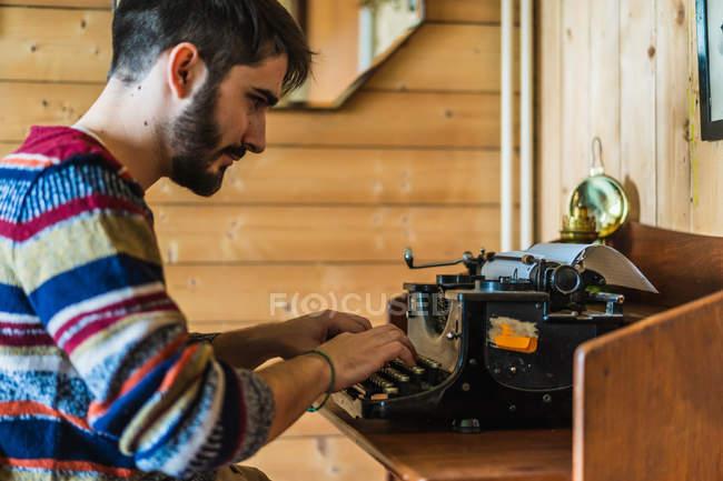 Вид на красивого бородатого мужчину в свитере, печатающего на ретро-машинке на деревянном столе дома . — стоковое фото
