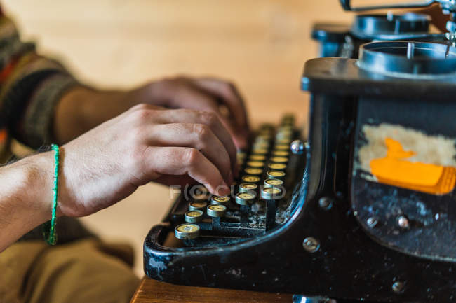 Side view of hands of man typing on retro typewriter on wooden table at home. — Stock Photo