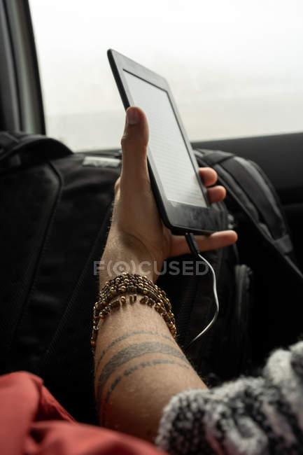 Mão masculina segurando e-book em viagens de carro . — Fotografia de Stock