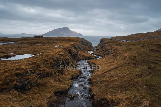 Ruisseau d'eau et route asphaltée sinueuse traversant un terrain vallonné pendant la journée nuageuse sur les îles Féroé . — Photo de stock