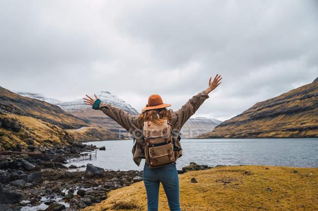 Visão traseira do viajante feminino estendendo os braços contra o mar azul e céu cinza durante a viagem em Ilhas Faroé. — Fotografia de Stock