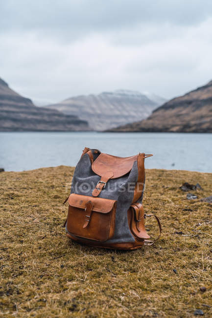 Stylish backpack on shore with dry grass by lake in mountains on Faroe Islands. — Stock Photo