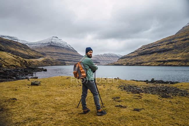 Visão traseira do homem em roupas de inverno olhando na câmera ao ar livre na paisagem das Ilhas Faroé . — Fotografia de Stock