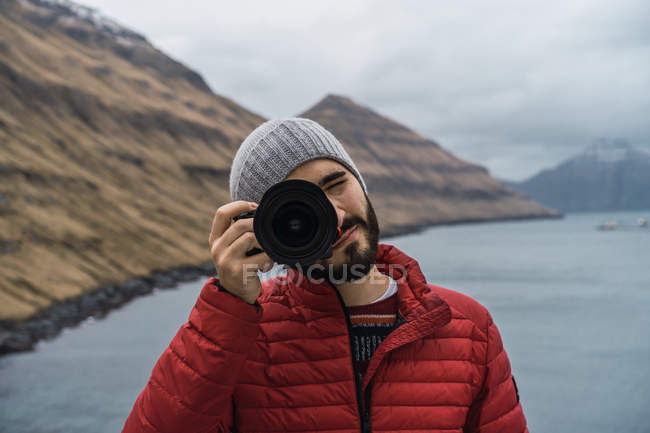 Bearded man in winter clothes using photo camera outdoors in Faroe Islands landscape. — Stock Photo