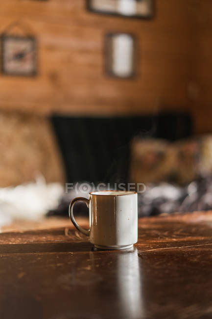 Mug of hot steamy beverage placed on wooden table in morning. — Stock Photo