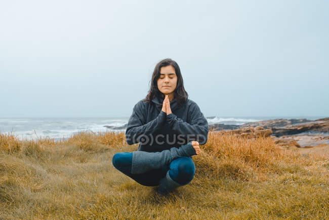 Молодая женщина практикует йогу, сидя у моря с закрытыми глазами — стоковое фото
