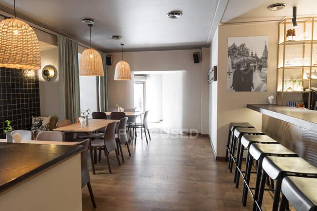 Elegante lámpara que brilla sobre pequeñas mesas y cómodas sillas en el acogedor restaurante - foto de stock