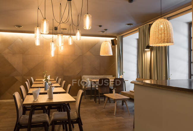 Stylish lamp shining over small tables and comfortable chairs in cozy restaurant — Stock Photo