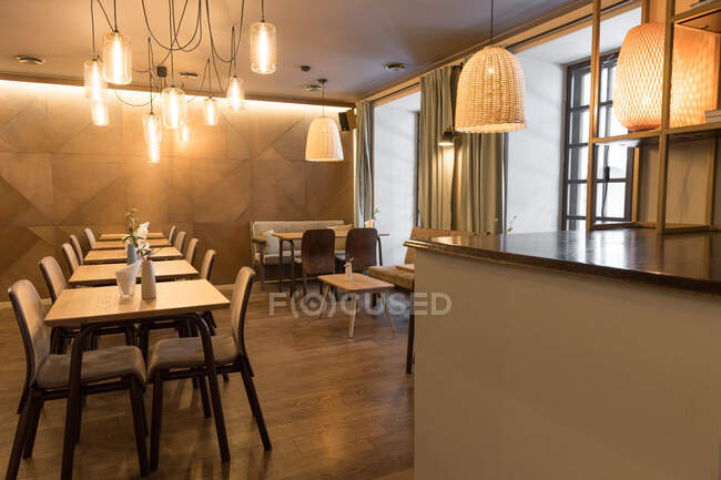 Стильова лампа світиться над малими столами і зручними стільцями в затишному ресторані. — стокове фото