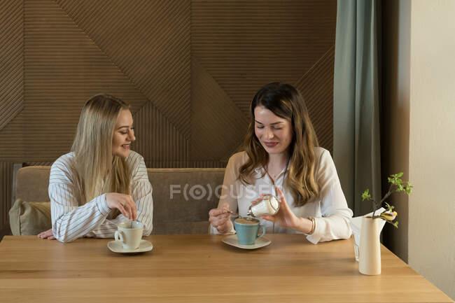Deux copines élégantes avec des tasses de café frais souriant et parlant tout en étant assis à la table dans un restaurant confortable — Photo de stock