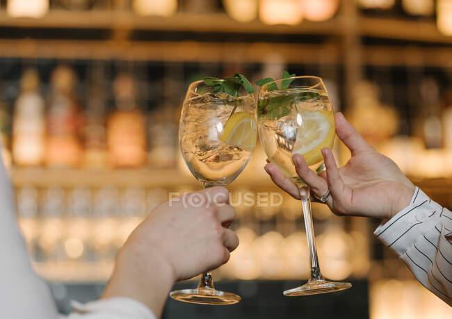 Вигляд анонімних жінок - друзів, які чіпляються за склянки алкогольних коктейлів, проводячи час у зручному ресторані. — стокове фото