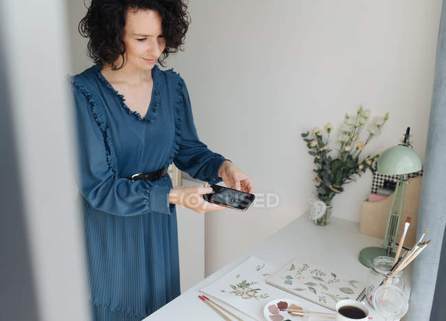 Художница в синем платье фотографируется на мобильном телефоне акварельной работы на столе в студии — стоковое фото