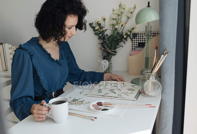 Brunette female artist sitting at table with cup of coffee and looking at drawing in workplace — стокове фото