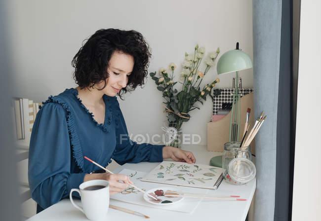 Элегантная женщина с кистью рисовать акварельные цветы на листе за столом — стоковое фото