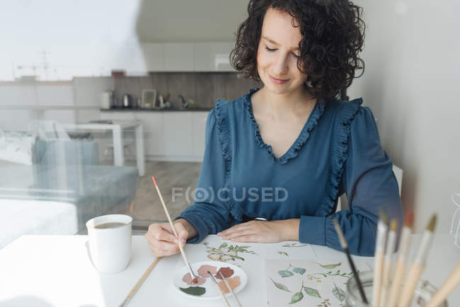 View through a window of elegant woman with brush painting watercolor flowers on sheet at desk — Stock Photo