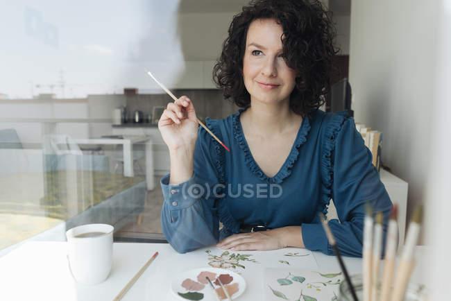 Вид через окно элегантной женщины с кистью рисовать акварельные цветы на листе на столе — стоковое фото