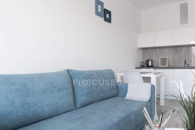 Salon moderne meublé avec murs blancs et plafond et canapé en bleu — Photo de stock