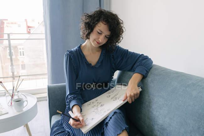 Elegante Frau, die zu Hause auf einem Sofa sitzt und Blumen auf einem Notizbuch zeichnet — Stockfoto
