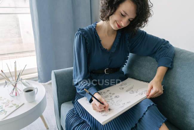 Elegant woman sitting on a sofa drawing flowers on a notebook at home — Stock Photo