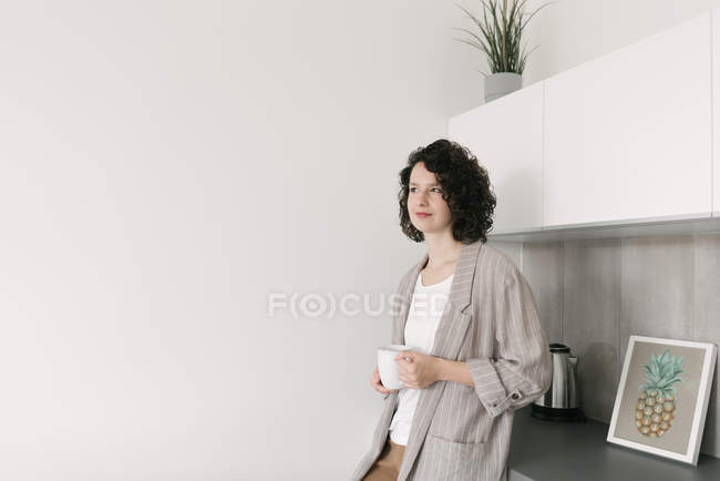 Mulher pensativa elegante na sala de visitas moderna com uma chávena de café — Fotografia de Stock