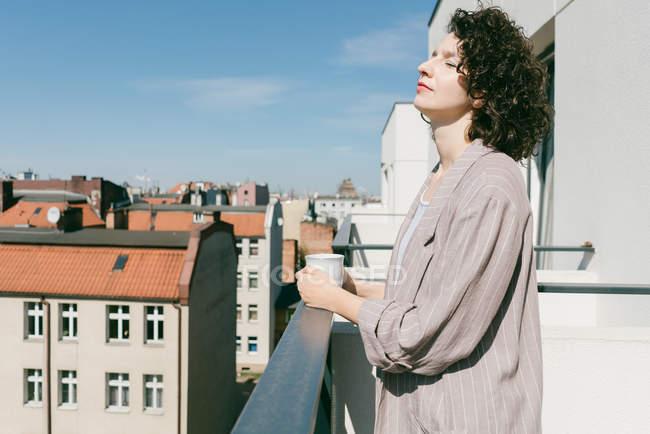 Elegante donna che si gode la luce del sole in terrazza con gli occhi chiusi mentre tiene una tazza di caffè — Foto stock