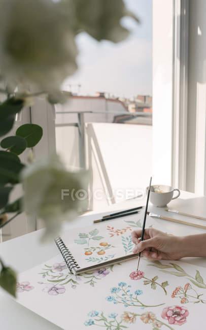 Abgeschnittene Person Hand mit Pinsel malen Aquarell Blumen auf Blatt am Schreibtisch — Stockfoto