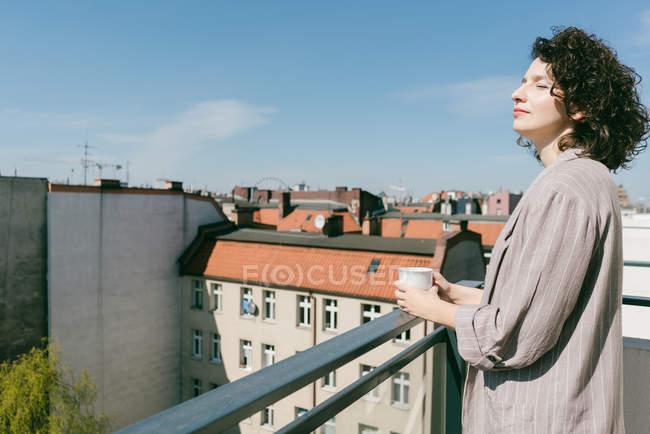Elegante Frau genießt Sonnenlicht auf der Terrasse mit geschlossenen Augen, während eine Tasse Kaffee halten — Stockfoto