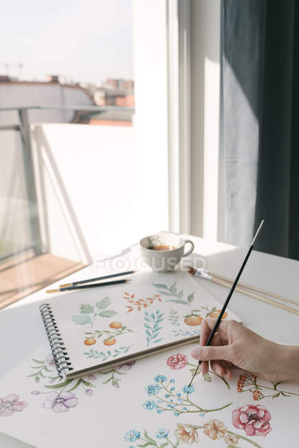 Cropped of person hand with brush painting watercolor flowers on large sheet at desk — Stock Photo