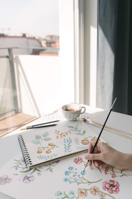 Cortado de la mano de la persona con la pintura del pincel flores de acuarela en hoja grande en el escritorio - foto de stock