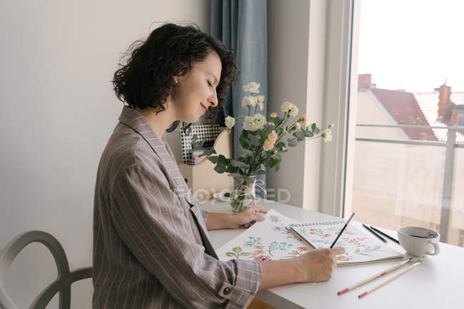 Elegant woman with brush painting watercolor flowers on large sheet at desk — Stock Photo