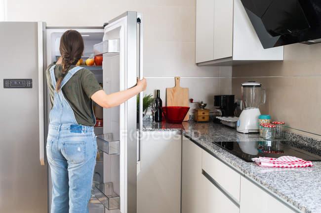 Unbekanntes Weibchen holt zu Hause frisches Obst aus Kühlregal — Stockfoto