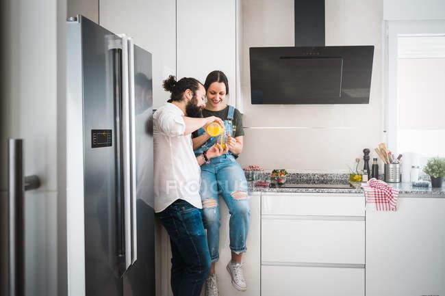 Одягнений чоловік годує дівчину здоровою їжею, а вдома разом на кухні. — стокове фото