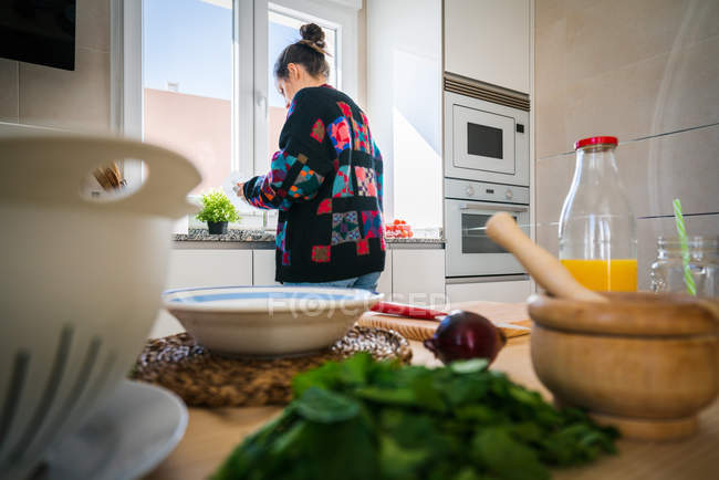 Anonymous female in colorful jacket washing fresh vegetable under clean water over sink in kitchen at home — Stockfoto