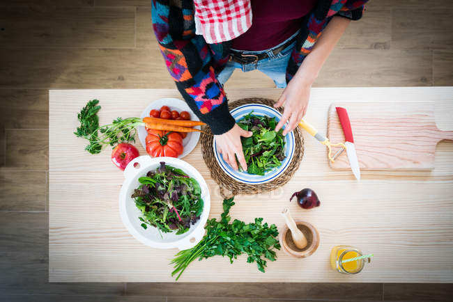 Hands of woman preparing vegetables while cooking healthy salad in kitchen — Stock Photo