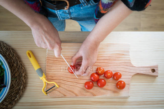 Cropped image of woman cutting tomatoes while cooking healthy salad in kitchen — Stock Photo