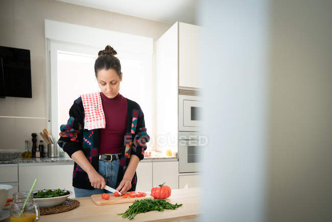 Anonymous woman cutting carrots while cooking healthy salad in kitchen — Stock Photo