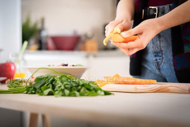 Imagen recortada de la mujer cortando zanahorias mientras cocina ensalada saludable en la cocina - foto de stock
