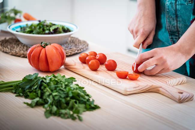 Abgeschnittenes Bild einer Frau, die Tomaten schneidet, während sie in der Küche gesunden Salat kocht — Stockfoto