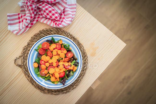 Bunter Salat mit Kirschtomaten in einer Schüssel auf dem Küchentisch — Stockfoto