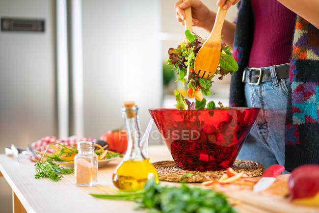 Imagem cortada da mulher em jaqueta multicolor misturando legumes em tigela enquanto cozinha salada saudável na cozinha — Fotografia de Stock