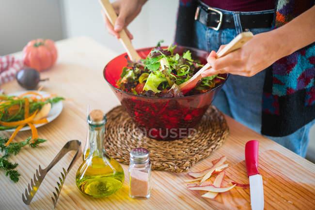 Abgeschnittenes Bild einer Frau in buntem Sakko, die Gemüse in einer Schüssel mixt, während sie in der Küche gesunden Salat kocht — Stockfoto