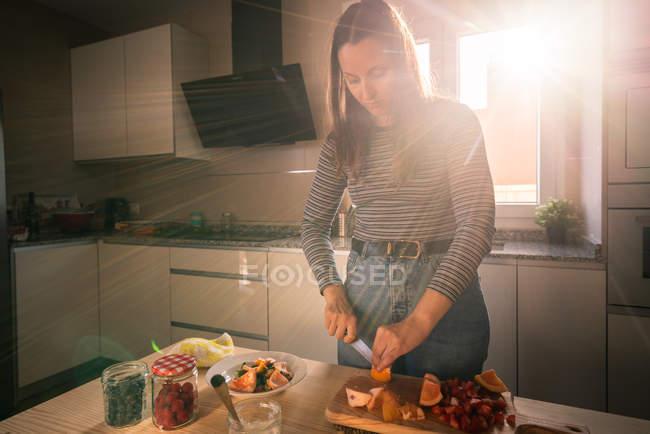Jovem fêmea em roupa casual cortando frutas frescas enquanto cozinha na cozinha aconchegante sob vigas de luz solar brilhante — Fotografia de Stock