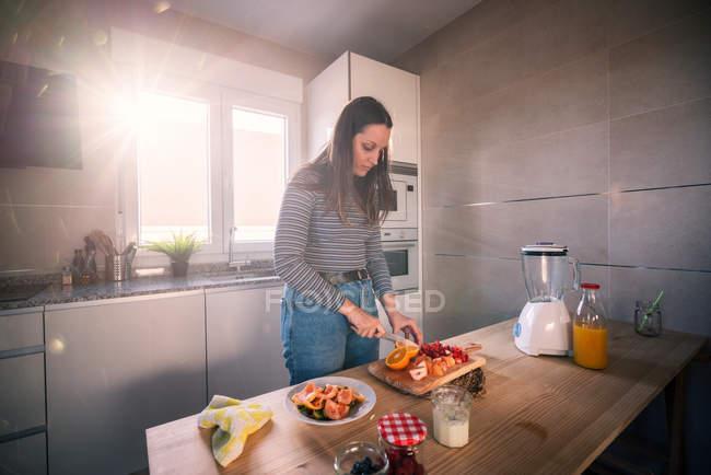 Giovane femmina in outfit casual tagliando frutta fresca durante la cottura in accogliente cucina sotto travi di luce solare — Foto stock