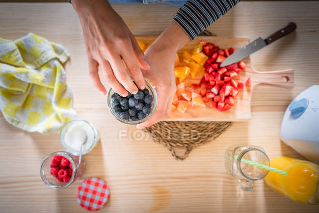 Cropped image of woman taking blueberries from jar while cooking healthy vitamin food from fresh fruits at home - foto de stock
