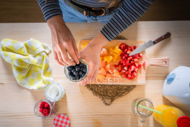 Cropped image of woman taking blueberries from jar while cooking healthy vitamin food from fresh fruits at home — Stock Photo