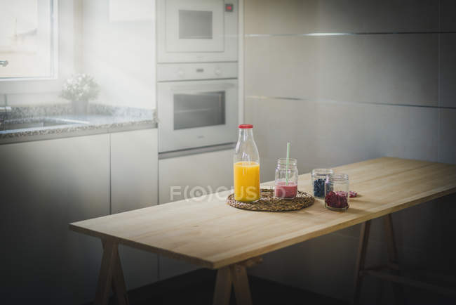 Containers with fresh berries and healthy beverages placed on table in modern kitchen — Stockfoto