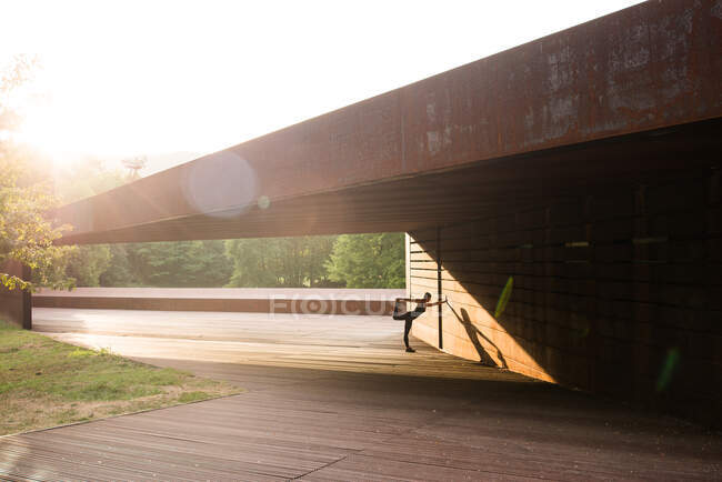 Young woman stretching after running and leaning in a amazing geometrical building — Stock Photo