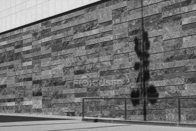 Маленькая тень камеры наблюдения на стене современного здания в солнечный день на городской улице — стоковое фото