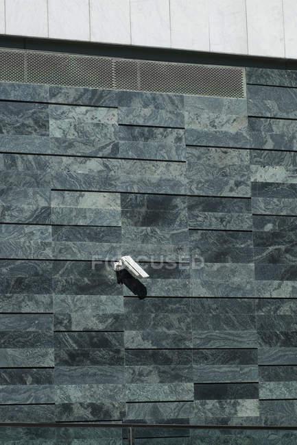 Небольшая камера наблюдения висит на стене современного здания на городской улице — стоковое фото