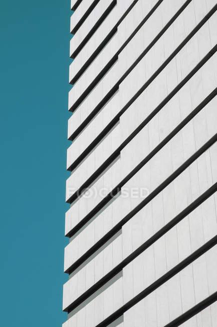 Стіна сучасного хмарочос проти безхмарне Синє небо в сонячний день на міській вулиці — стокове фото